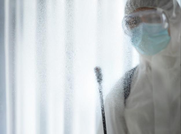 Homem no terno protetor e desinfecção da máscara no vidro no quarto de hospital do vírus corona / covid-19.