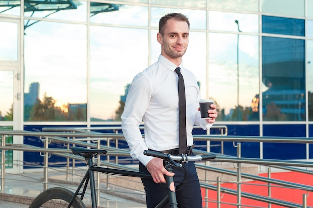 Homem no terno que guarda uma xícara de café que anda pela rua com sua bicicleta.