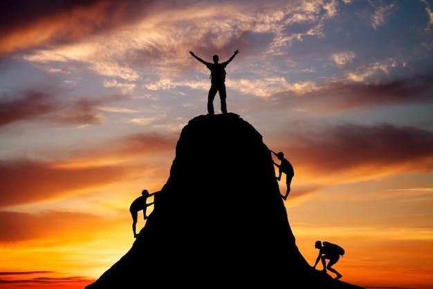 Homem no topo da montanha e as outras pessoas para escalar em um fundo laranja ardente. alpinista no fundo do sol. esporte e vida ativa.