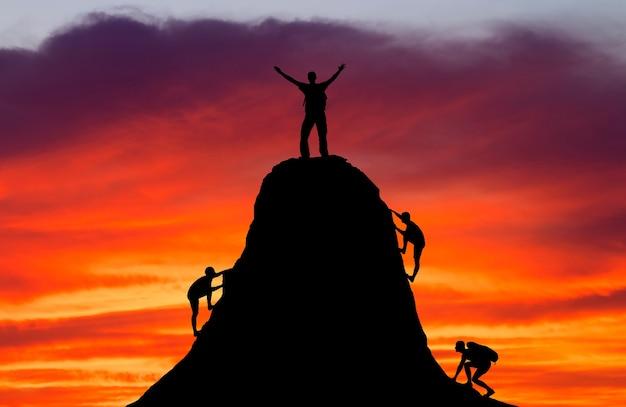 Homem no topo da montanha e as outras pessoas para escalar. esporte e vida ativa.