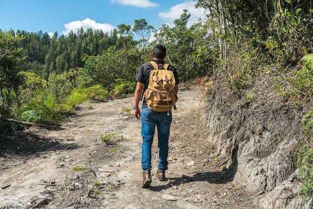 Homem no topo de uma montanha com as mãos para cima