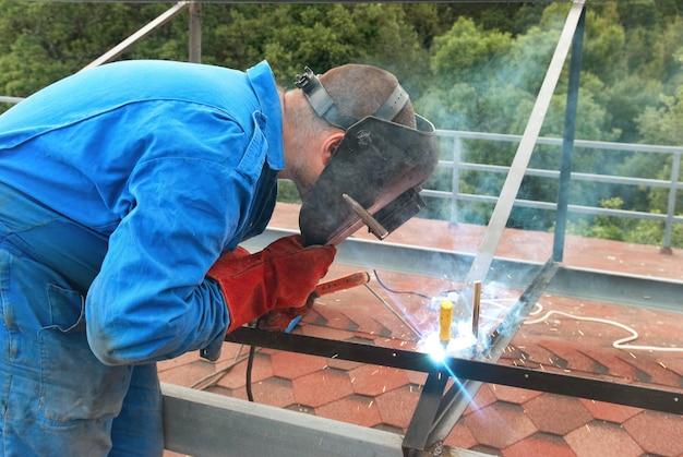 Homem no trabalho: soldador no canteiro de obras trabalhando com construção metálica