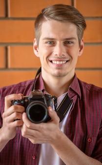 Homem no vestuário desportivo esperto que guarda a câmera e o sorriso.