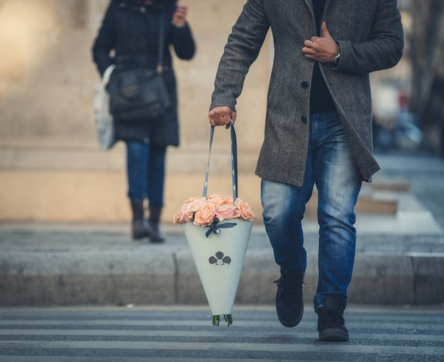 Homem no wtreet andando com um buquê de flores portátil.