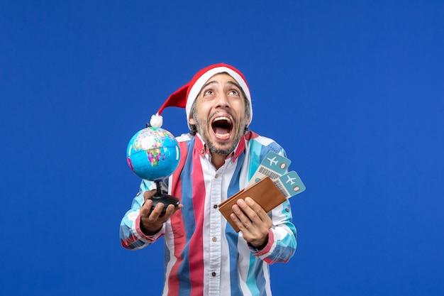 Homem normal de vista frontal com ingressos e globo na mesa azul, cor de feriado, ano novo