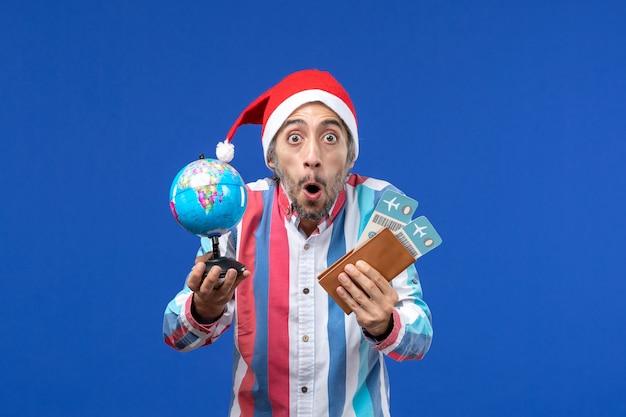 Homem normal de vista frontal com ingressos e globo no piso azul, cor do feriado de ano novo
