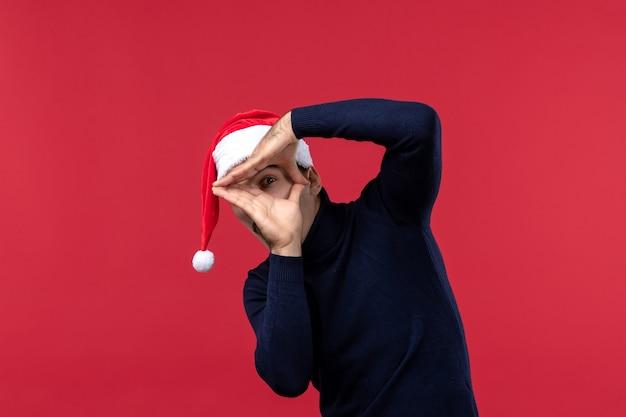 Homem normal de vista frontal olhando por entre os dedos em fundo vermelho