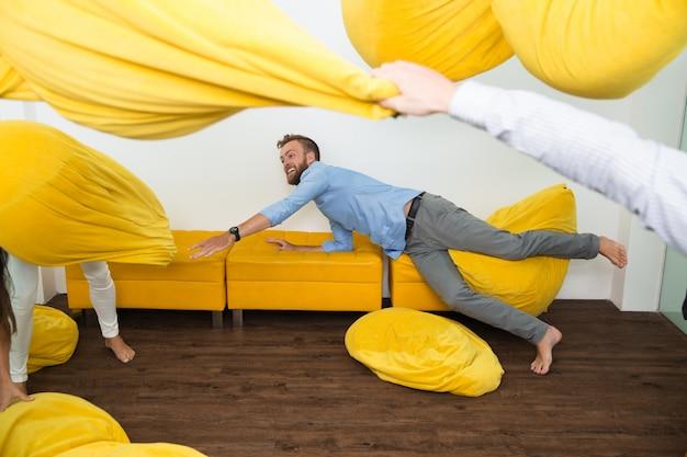 Homem novo alegre no sofá entre os puffs voando