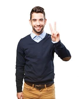 Homem novo alegre que mostra o gesto da vitória