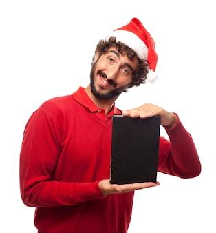 Homem novo alegre que mostra um livro