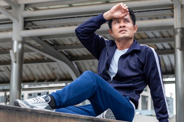 Homem novo asiático ativo cansado e descansando durante o exercício na rua ao ar livre.