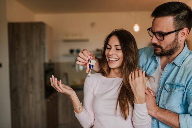 Homem novo atrativo que surpreende sua esposa com uma chave a seu apartamento novo.