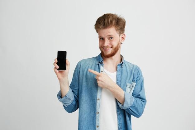 Homem novo bonito alegre que sorri apontando o dedo no smartphone em sua mão sobre o fundo do wite.