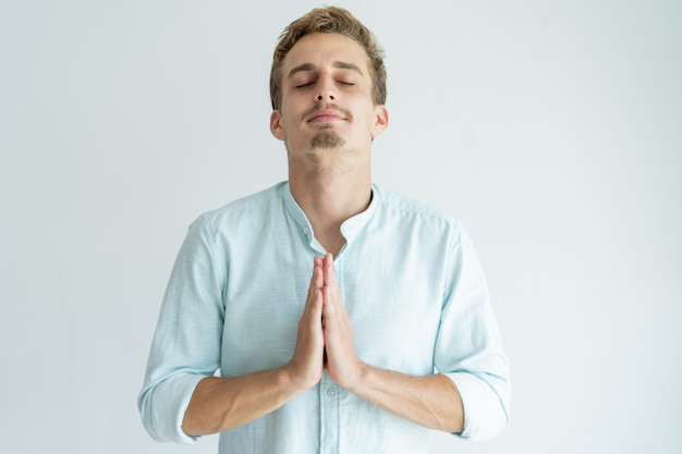 Homem novo calmo que reza com seus olhos fechados e que mantém as mãos unidas.