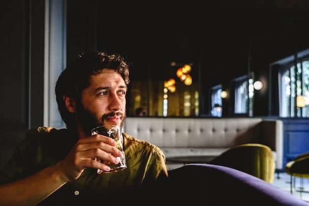 Homem novo com a barba latin que olha ao infinito que pensa sobre o negócio futuro com uma bebida em sua mão.
