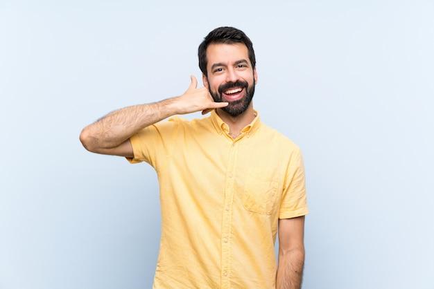 Homem novo com a barba sobre o gesto de fatura azul isolado do telefone. me ligue de volta