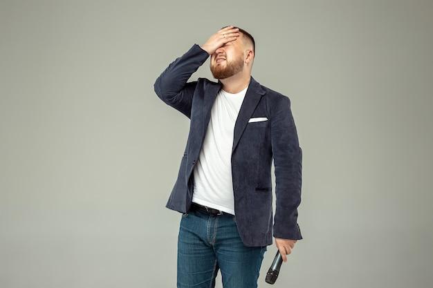 Homem novo com o microfone no estúdio cinzento, conceito principal.