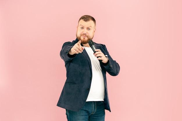 Homem novo com o microfone no rosa, conduzindo com o microfone no conceito do estúdio.