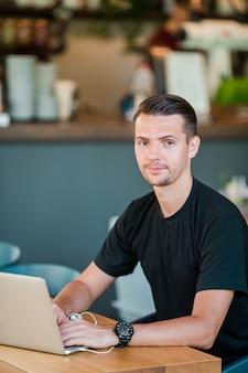 Homem novo com o portátil no café bebendo do café ao ar livre. homem usando smartphone móvel.