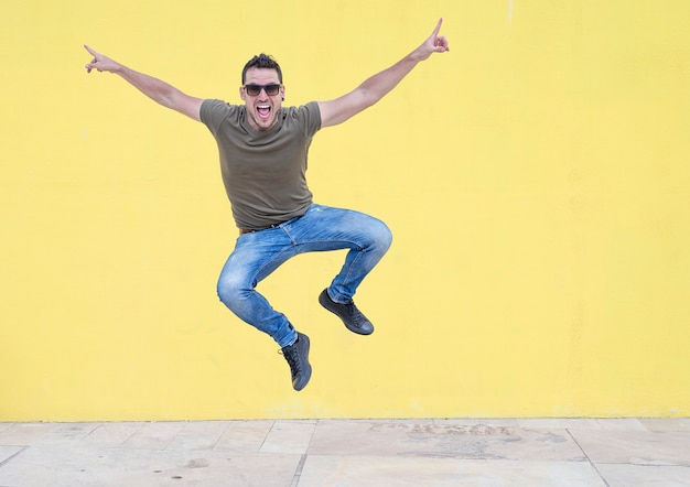 Homem novo com os óculos de sol que saltam na frente de uma parede amarela.