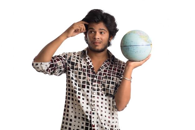 Homem novo com um globo do mundo em um fundo branco.