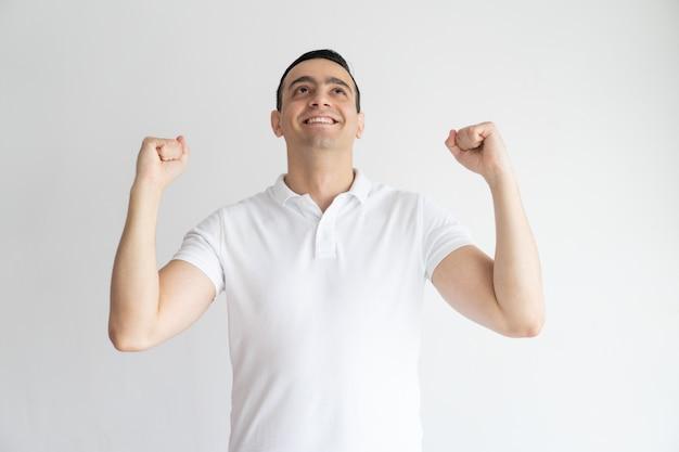 Homem novo considerável entusiasmado que comemora o sucesso e que faz sim o gesto.