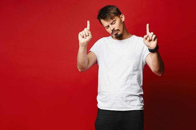 Homem novo considerável que aprecia a música e que dança sozinho em um fundo vermelho, isolado.