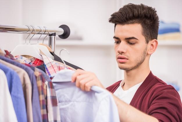 Homem novo considerável que escolhe a camisa no vestuário.