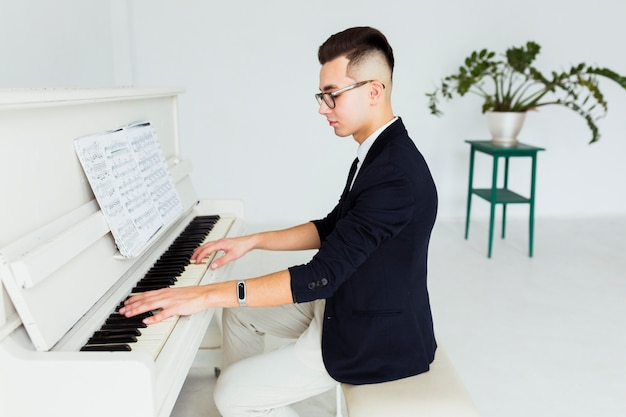 Homem novo considerável que joga o piano olhando a folha musical