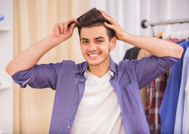 Homem novo considerável que penteia seu cabelo no vestuario.