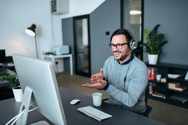Homem novo considerável que tem a chamada em linha no escritório moderno.