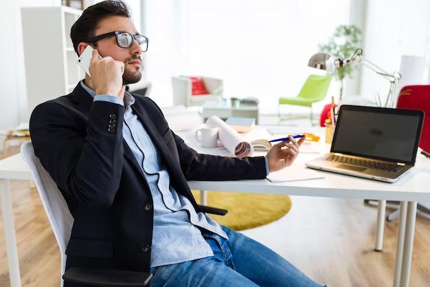 Homem novo considerável que usa seu telefone móvel no escritório.