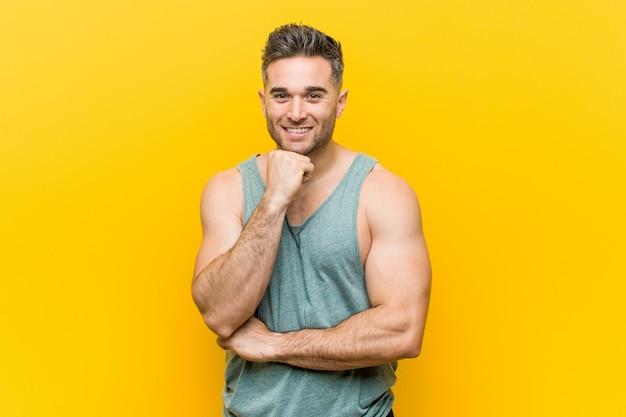 Homem novo da aptidão contra um fundo amarelo que sorri queixo feliz e seguro, tocante com mão.