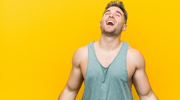 Homem novo da aptidão contra uma parede amarela relaxado e riso feliz, pescoço esticado mostrando os dentes.