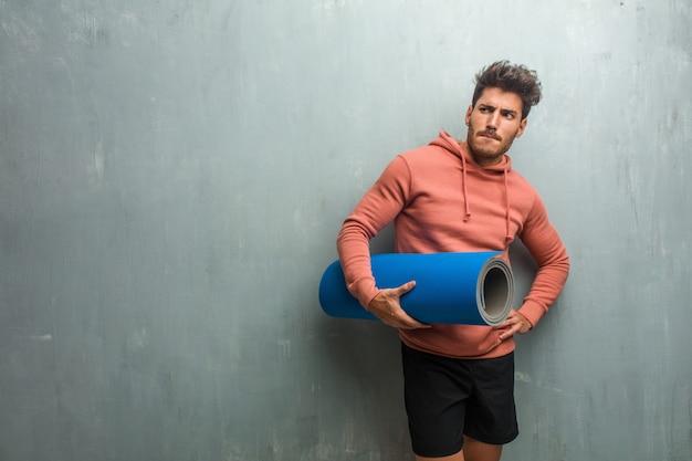 Homem novo da aptidão contra uma parede do grunge que duvida e confuso, pensando de uma ideia ou preocupado sobre algo. segurando um tapete azul para praticar yoga.