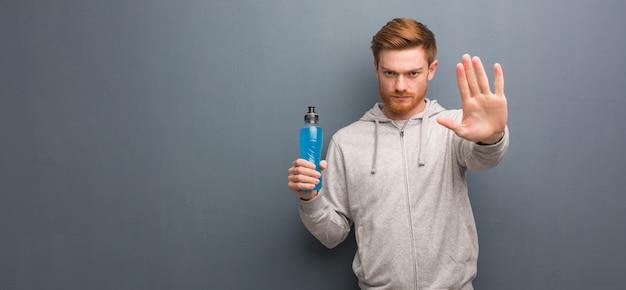 Homem novo da aptidão do ruivo que põe a mão na parte dianteira. ele está segurando uma bebida energética.