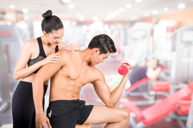 Homem novo da aptidão e sua amiga no gym do treinamento. fitness e conceito de estilo de vida saudável