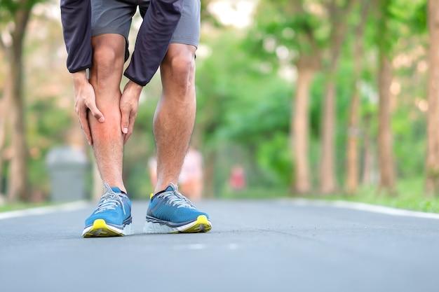 Homem novo da aptidão que guarda seus ferimento de pé dos esportes.