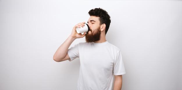 Homem novo da barba que bebe o café ou o chá de um copo de papel no fundo branco. tire o café.