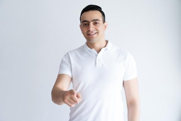 Homem novo de sorriso que aponta em você e que olha a câmera. cara, escolhendo o visualizador.