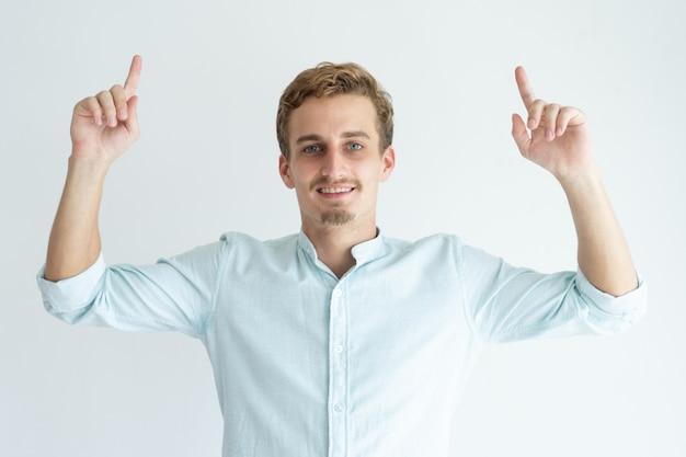 Homem novo de sorriso que aponta os dedos indicadores para cima. cara bonito, recomendando algo.