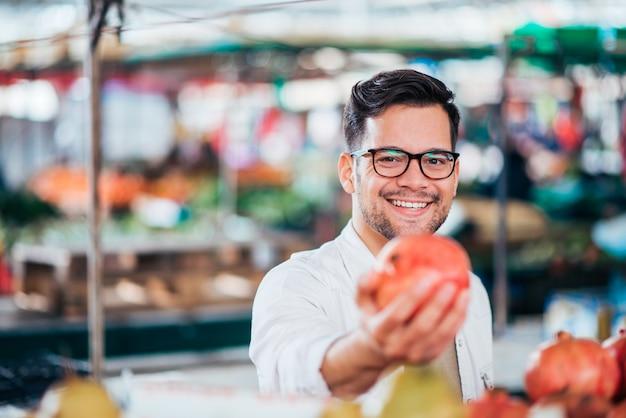 Homem novo de sorriso que guarda a maçã no mercado do fazendeiro.