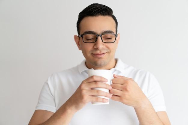 Homem novo de sorriso que guarda o chá da caneca, cheirando e bebendo.