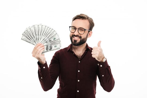 Homem novo de sorriso que mantém o dinheiro que mostra os polegares.