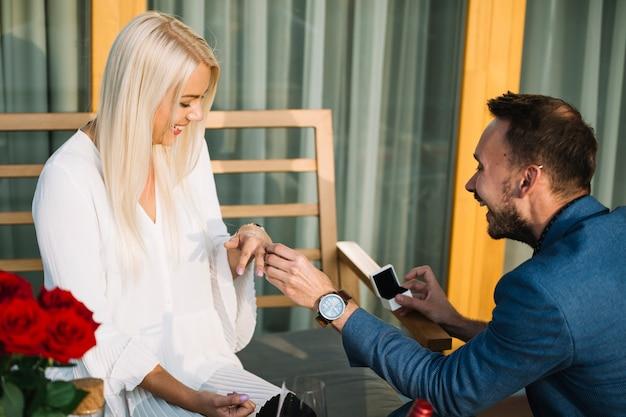 Homem novo de sorriso que põe o anel de noivado no dedo da amiga