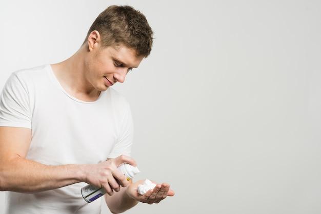 Homem novo de sorriso que pulveriza a espuma de rapagem em sua mão contra o fundo branco