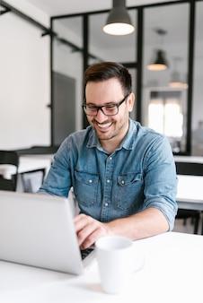 Homem novo de sorriso que usa o portátil no escritório moderno.