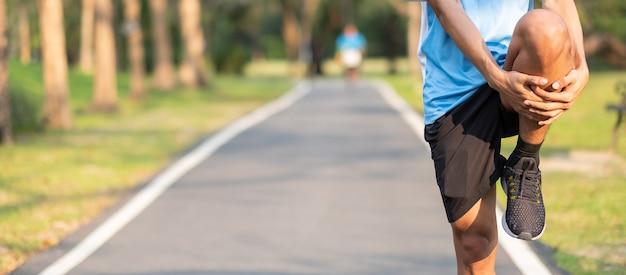 Homem novo do atleta que streching no parque ao ar livre.