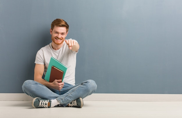 Homem novo do estudante do ruivo que senta-se no assoalho alegre e que sorri apontando à parte dianteira.
