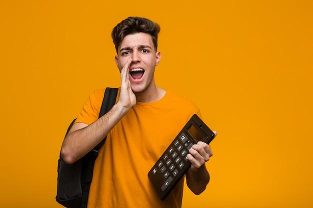 Homem novo do estudante que prende uma calculadora que sorri alegremente apontando com dedo indicador afastado.